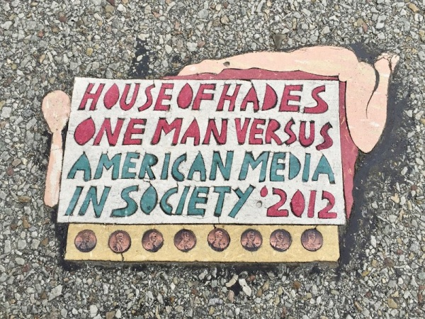 "Street art ""Toynbee tile"" reading ""House of Hades, one man versus American media in society: 2012"", Pittsburgh, PA"