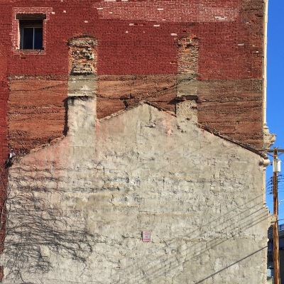 "outline of previously-existing ""ghost house"" against larger brick building, Pittsburgh, PA"