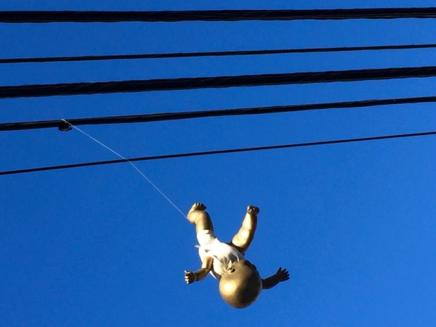 baby doll painted gold and hanging from telephone wires, Pittsburgh, PA