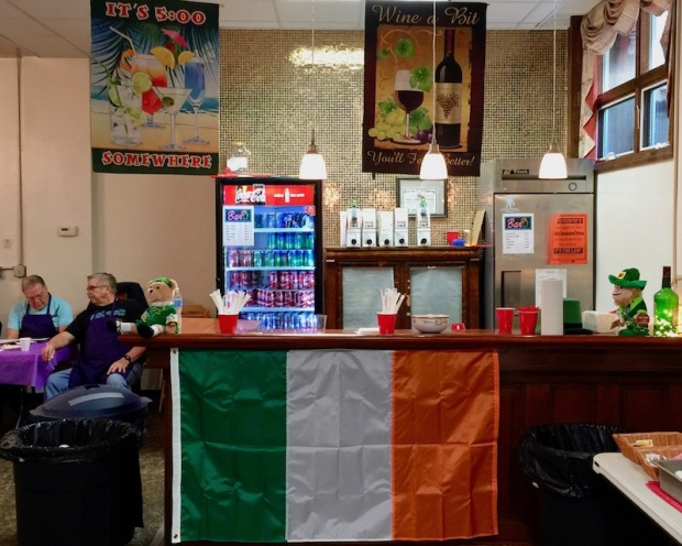 small bar in church basement decorated with flag and banners