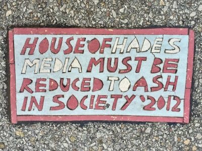 "Street art ""Toynbee tile"" reading ""House of Hades, media must be reduced to ash in society: 2012"", Pittsburgh, PA"
