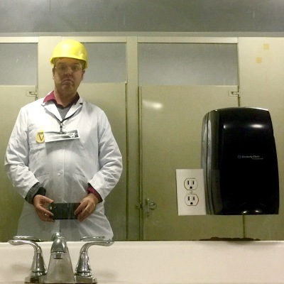 man in lab coat and hard hat in employee restroom