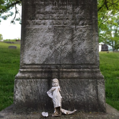 broken porcelain doll on base of marble grave monument, Allegheny Cemetery, Pittsburgh, PA