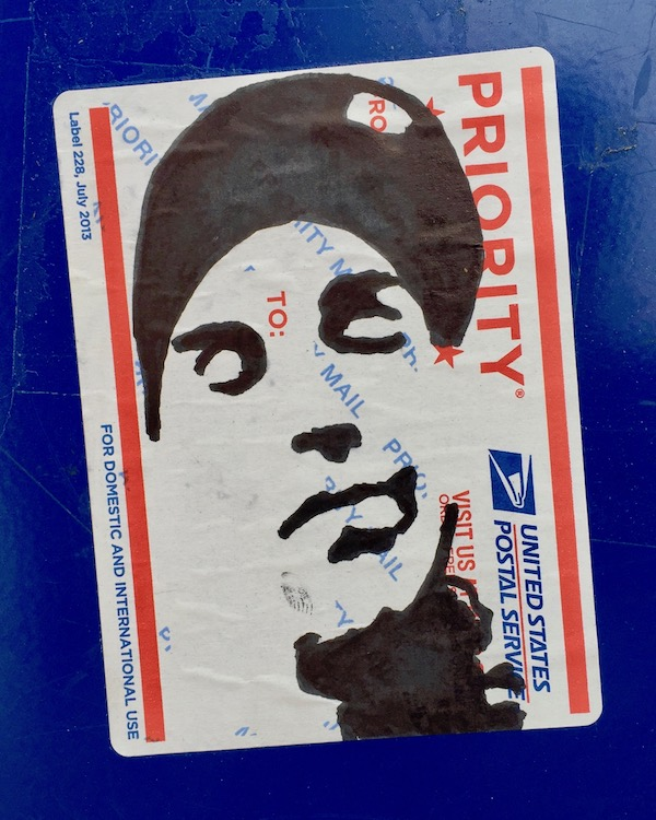 portrait of man with eyes closed wearing a baseball cap drawn on US postal service mail label and stuck to blue free paper box, Pittsburgh, PA