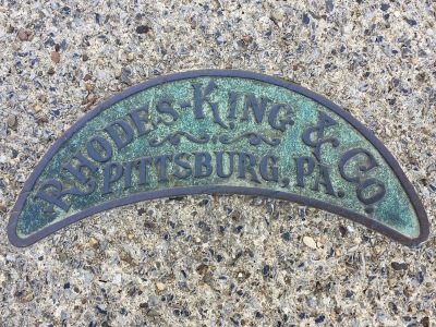 brass plate embedded in sidewalk concrete advertising Rhodes-King & Company, Pittsburgh, PA