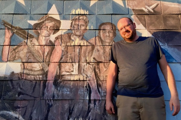Poet Scott Silsbe standing in front of faded mural of Viet Nam veterans, Pittsburgh, PA