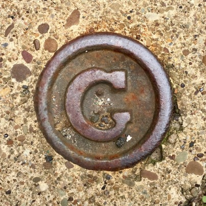 "round steel sidewalk plaque with letter ""G"", Pittsburgh, PA"