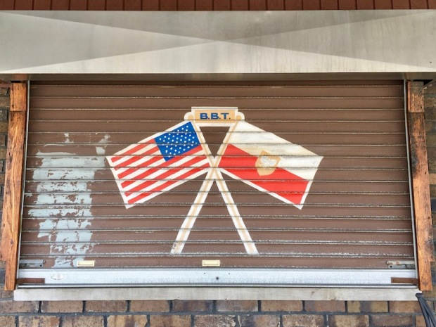 metal rolling window cover painted with crossed American and Polish flags, Pittsburgh, PA