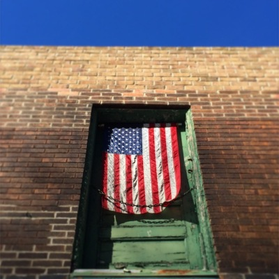 American flag hanging in second-floor doorway of brick house, Pittsburgh, PA
