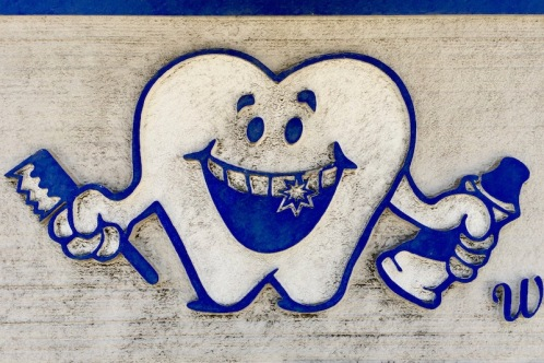 anthropomorphized smiling tooth with toothbrush and toothpaste from a sign for McKees Rocks Dental, McKees Rocks, PA