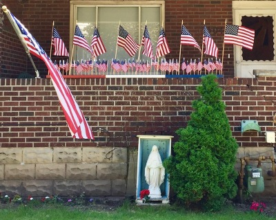 Mary statue in front of brick porch with many American flags, Pittsburgh, PA
