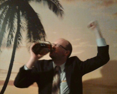 author Scott Silsbe dressed in suit and tie, drinking whiskey from a bottle in front of a wallpaper beach scene