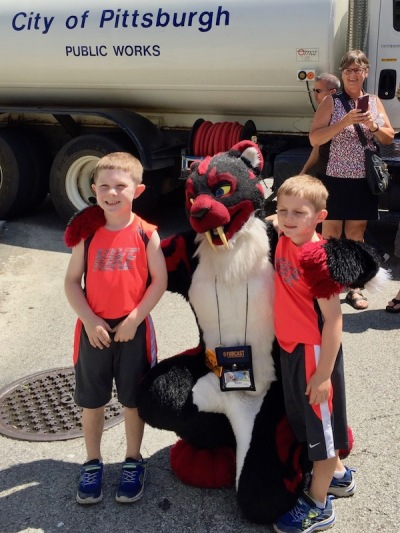 two children posing for photograph with person in fursuit costume of sabretooth tiger at Anthrocon 2017 Fursuit Parade, Pittsburgh, PA