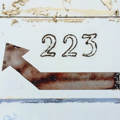 tile building facade with number 223 and arrow directing around the back, Homestead, PA