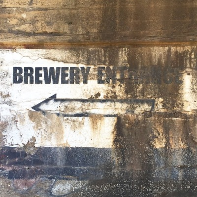 sign for brewery entrance with directional arrow painted on bridge support, Pittsburgh, PA