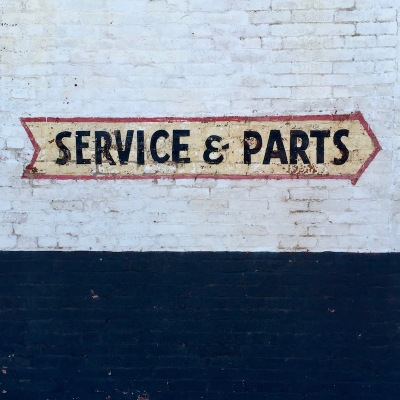 """Service & Parts"" sign painted in shape of an arrow on brick wall, Pittsburgh, PA"