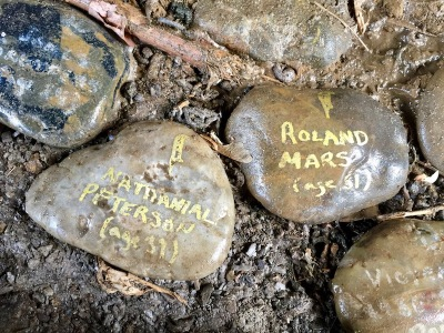 "river stones painted with white text reading ""Nathanial Peterson (age 39)"" and ""Roland Mars (age 31)"", Pittsburgh, PA"