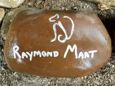 "river stone painted with white text reading ""Raymond Maat"", Pittsburgh, PA"