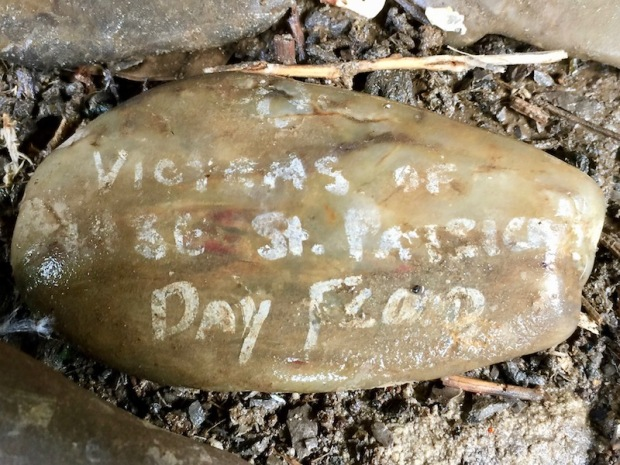 """river stone painted with white text reading """"Victims of 1936 St. Patrick's Day Flood"""", Pittsburgh, PA"""