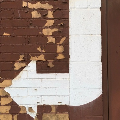 white arrow painted on brown brick and cinderblock wall, McKeesport, PA