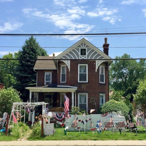 brick house with many handmade wood cut Independence Day lawn decorations, Beaver, PA