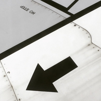 detail of arrow painted on the wing of an airplane