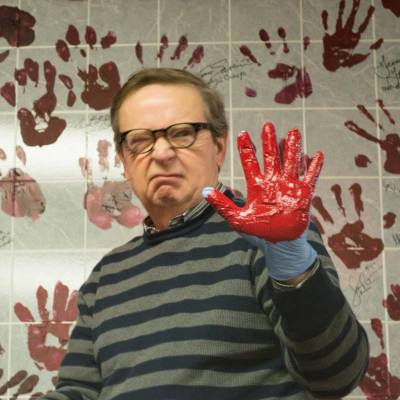 John Kirch with left hand painted blood red, preparing to leave a hand print on wall