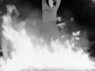 "still from ""Night of the Living Dead"" with zombies recoiling from fire"