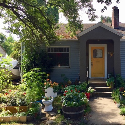 small house with front yard planters made from a toilet, dresser drawers, wooden boxes, Portland, OR