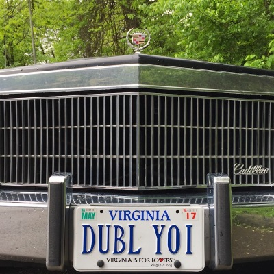 "front grill of a 1970's Cadillac with ""DUBL YOI"" Virginia license plate"