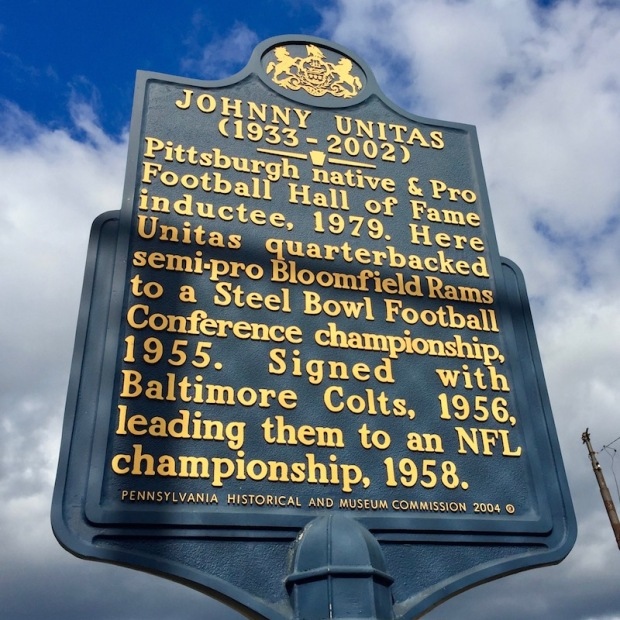 "historical plaque honoring Johnny Unitas that reads ""(1933-2002) Pittsburgh native & Pro Football Hall of Fame inductee, 1979. Here Unitas quarterbacked semi-pro Bloomfield Rams to a Steel Bowl Football Conference championship, 1955. Signed with Baltimore Colts, 1956, leading them to an NFL championship, 1958."