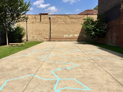 blue line painted on cement of Grant Avenue Pocket Park, Millvale, PA