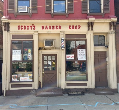 blue line painted on sidewalk in front of Scott's Barber Shop, Millvale, PA