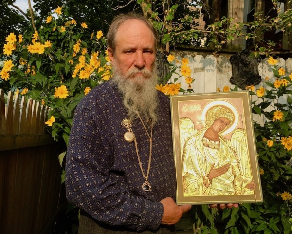 icon painter Simeon Larivonovoff holding a glowing icon of the Arcangel Michael