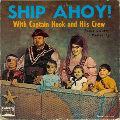 """album cover for Captain Hook and His Crew's """"Ship Ahoy!"""" with a couple and three childen plus one dummy in a prop row boat"""