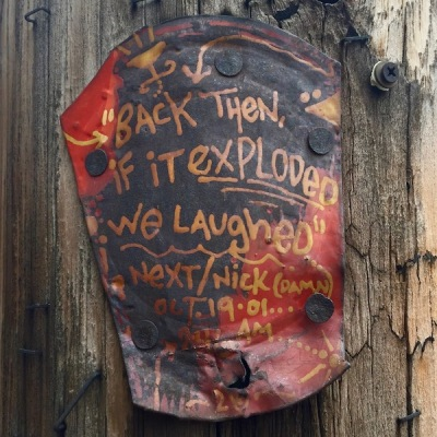 "Cut tin can painted with text and nailed to telephone pole. Text reads ""Back then, if it exploded, we laughed"", Pittsburgh, PA"