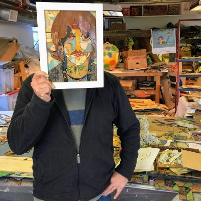artist Bill Miller holding his linoleum portrait of George Harrison in his Pittsburgh art studio
