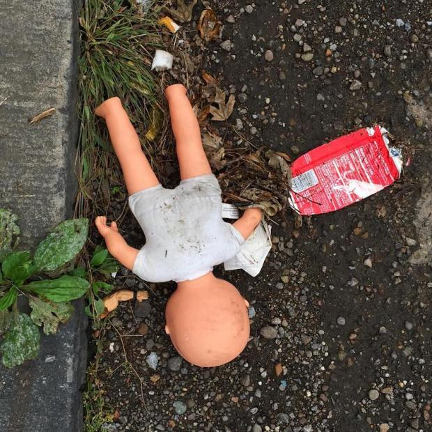 baby doll laying face down on street, Pittsburgh, PA