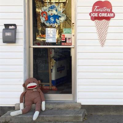 large stuffed animal made to look like a sock monkey laying in business doorway, Pittsburgh, PA