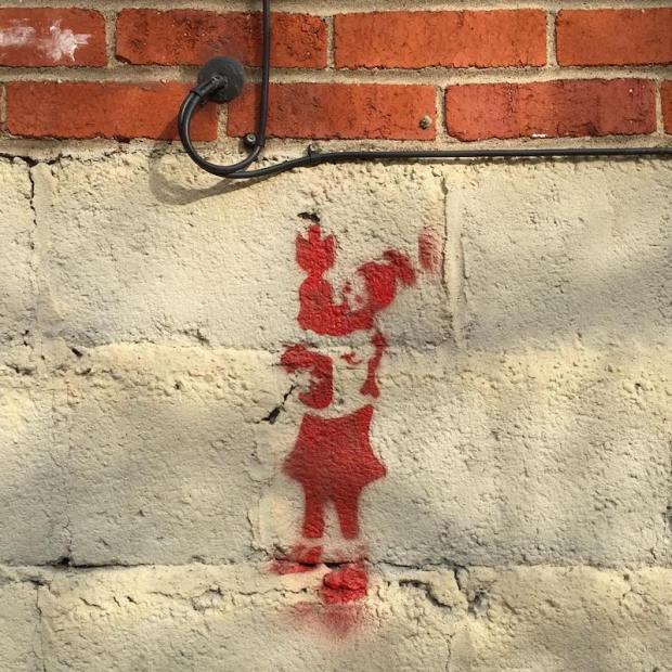 stencil image of person cradling a bomb painted on cinderblock wall, Pittsburgh, PA