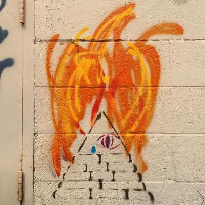 stencil image of pyramid with eyeball on fire painted on cinderblock wall, Pittsburgh, PA