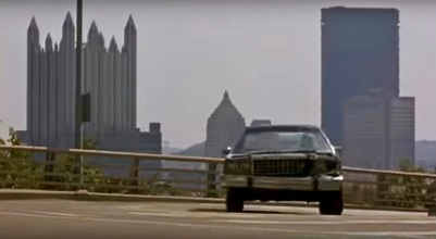 "scene from the film ""Striking Distance"" of car on street in front of downtown Pittsburgh, PA skyline"