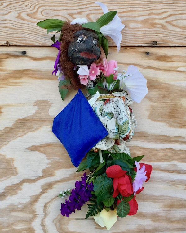 sculpture of black plaster head with flowers attached to wood