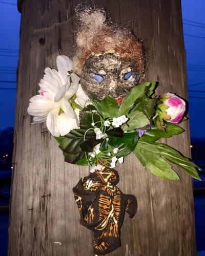 sculpture of black plaster head with golden hair and flowers attached to utility pole
