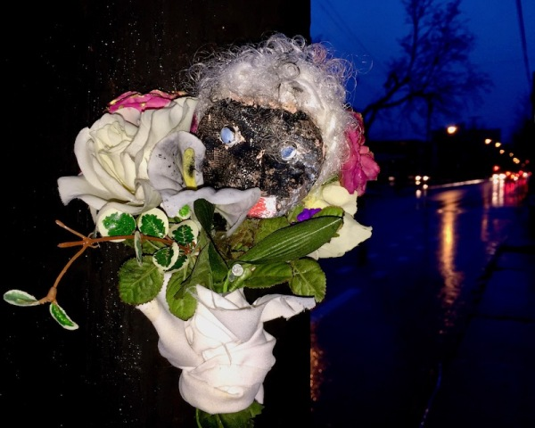 sculpture of black plaster head with fake white hair and flowers attached to utility pole