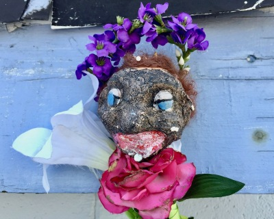 sculpture of black plaster head with fake flowers