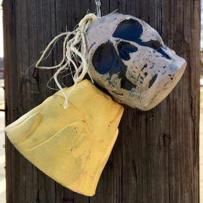skull and bell attached to utility pole