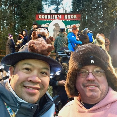 Two men wearing groundhog hats in front of Gobbler's Knob stage on Groundhog Day