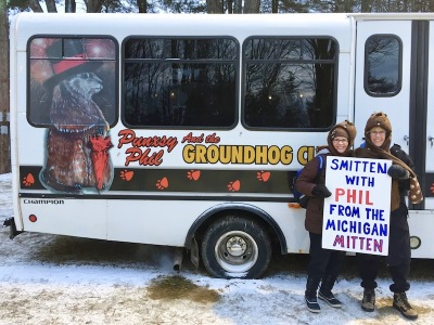 "two women holding a sign reading ""Smitten with Phil from the Michigan mitten"" at Groundhog Day"