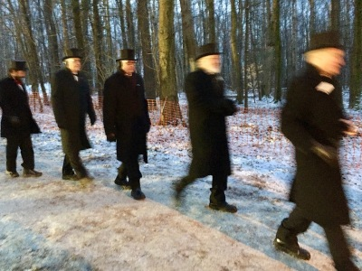 Five men dressed in black pants, long coats, and top hats walk through winter woods